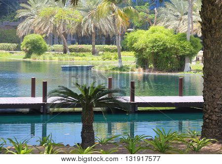 A blue lake in a nice tropical park with a small boat