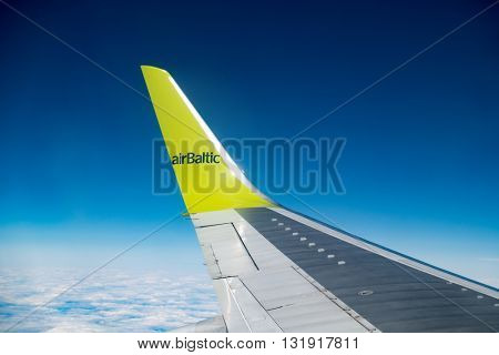 RIGA, LATVIA - MAY, 25, 2016: Aircraft wing,  Clouds skies above and below. AS Air Baltic Corporation,  is the Latvian flag carrier airline and a low-cost carrier