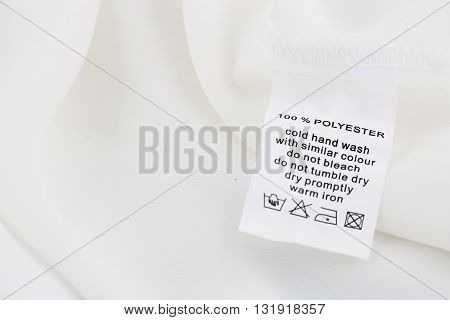 Fabric composition and washing instructions label on white shirt
