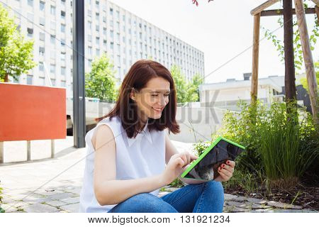 Smiling young woman student taping on tablet using tablet in campus university.Young smiling student outdoors with tablet.Life style.City