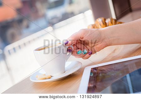 View of a womans hand reaching out to take a cup of rich espresso coffee. breakfast with cup of coffee