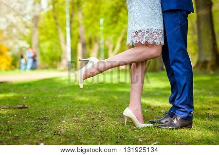 Wedding couple standing in the park on grass. Focus on legs