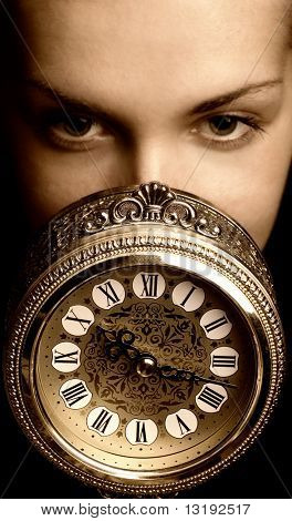 Sepia picture of a girl's face with a clock (focus on clock)