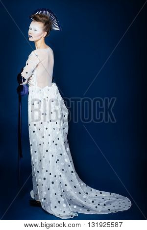 Full body shot of Japanese young woman in fashion elegant designers grey dress and blue velvet gloves on blue blackground