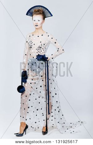 Full body shot of Japanese young woman in fashion elegant designers grey dress and blue velvet gloves on grey blackground