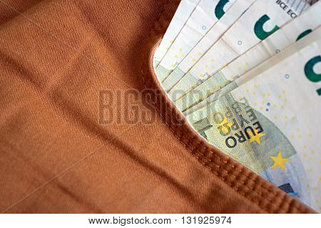stack money Euro in orange jeans pocket
