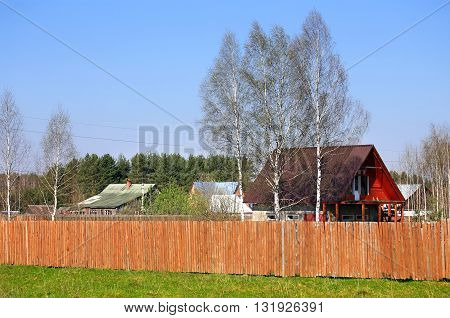 Wooden cottages among the trees behind the fence