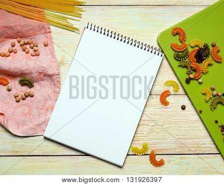 White notebook with spices and noodles on yellow wooden background. kitchen concepts