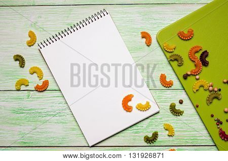 White notebook with spices and noodles on green wooden background. kitchen concepts