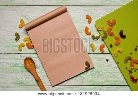 brown notebook with spices and noodles on green wooden background, cookbook and spoon on the table