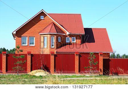 New red brick cottage behind metallic fence