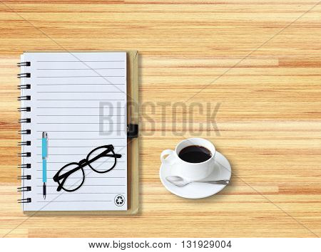 Notebook with office supplies with pen with glasses and cup of coffee on wooden table.