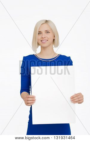 Young smiling woman in blue dress show blank card or paper on white background.