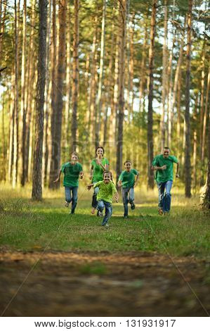 Happy cheerful family running in summer park