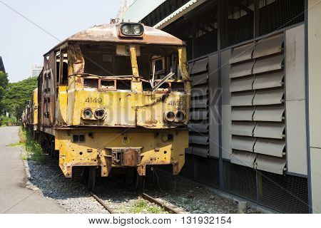 The ancient train has yellow or rust on the old railway near that has rocks and grass and behind has sky tree and buildings.