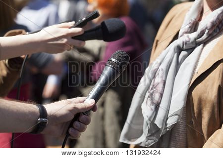 Reporters holding a microphone conducting an TV or radio interview. News conference.