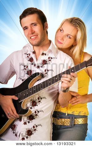 Young musician plays guitar and beautiful blond girl stands nearby