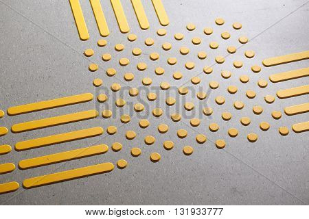 Tactile paving with textured ground surface with markings indicators for blind and visually impaired. Blindness aid visual impairment independent life concept.