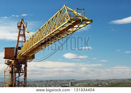 Construction crane tower against a blue sky