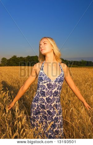 Beautiful girl in the wheat field at sunset time