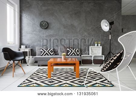 Living room with grey walls and white wooden parquet. Black and white decorations with orange coffee table in the middle of the room