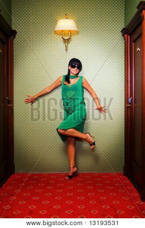 Schöne Brünette in einem grünen Kleid Ruf in der Nähe von der Wand