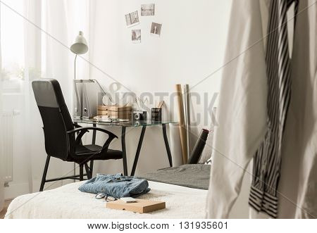 Modern bedroom of a young designer arrangged in light colours with a lot of personal items
