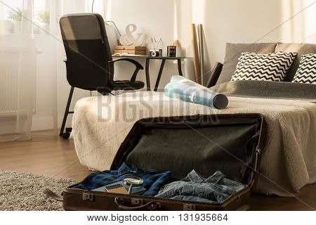 Man's bedroom arranged in natural style filled with items connected with travelling with vintage suitcase in the foreground