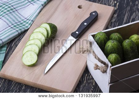 Fresh cucumbers, knife and slices on the wooden table