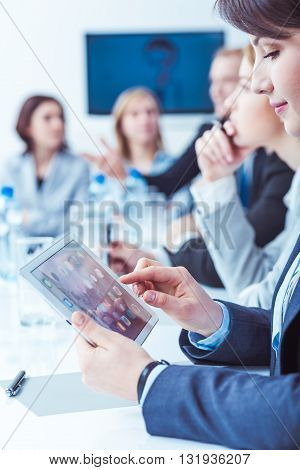 Young pretty woman using new tablet during company business meeting. Talking about company strategy
