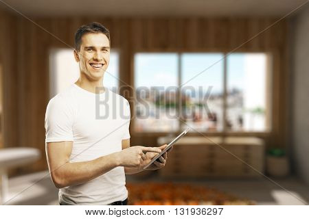 Young man using tablet in room. Mock up