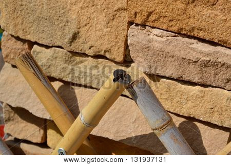 bamboo fence in front of brick wall