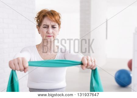 Mature woman exercising with tape in light interior