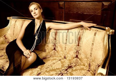 Sexy blond girl sitting on a luxury sofa (toned in sepia)