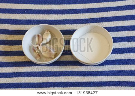 salt and garlic in saucer on white blue textile