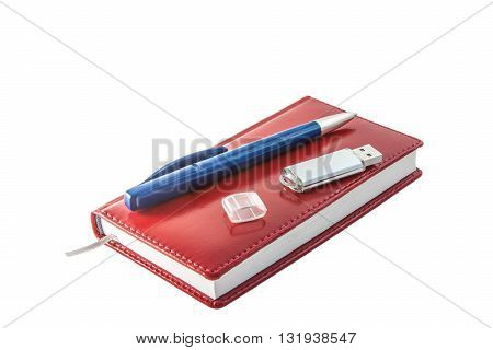 red notebook with a blue ball pen and usb the flash drive on a white background