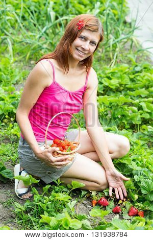 woman in garden with strawberry
