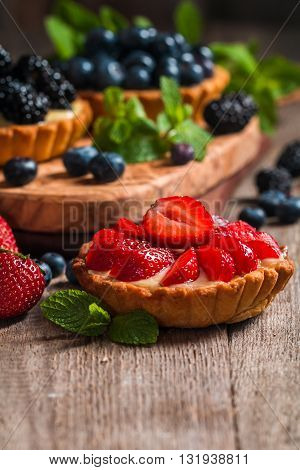 Fresh homemade berrie tarts with blueberries, blackberry and strawberries on wooden background