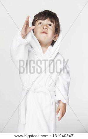 Cute little boy in a white Bathrobe on white background