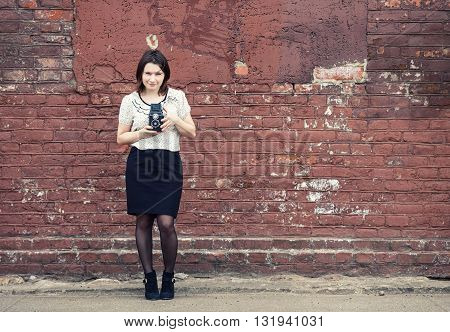 Woman photographer holding retro camera and taking photo on vintage brick wall background. Toned photo with copy space. Vintage style photo.