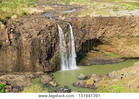 BAHIR DAR, ETHIOPIA - JANUARY 21, 2010: Unidentified people enjoy the view to the waterfall at the Blue Nile river in dry season in Bahir Dar, Ethiopia.