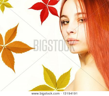Beautiful girl with a red hair and colorful autumn leaves around her