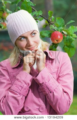 Young girl in pink coat near the apple tree