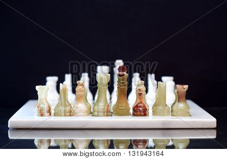 Set of chess pieces made from Onyx on board against dark background