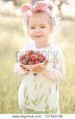 Smiling child girl 4-5 year old eating strawberry outdoors. Looking at camera. Summer season.