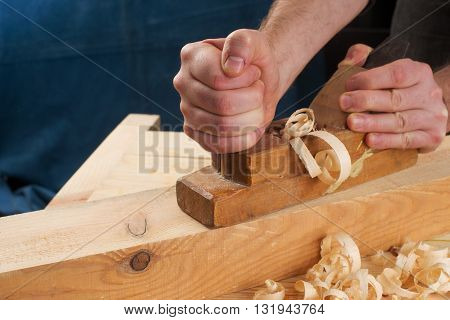 Carpenter working with plane on wooden background. Copy space. Top view.