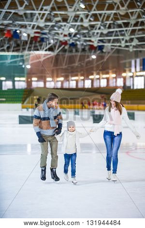 Smiling family skating at ice rink