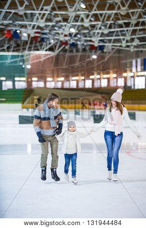 Smiling family skating at ice rink