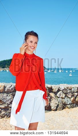Smiling Woman Speaking Smartphone In Front Of Lagoon With Yachts