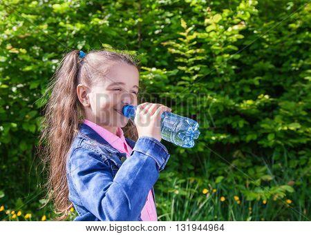 girl in a blue denim jacket drinks water from a plastic bottle outside